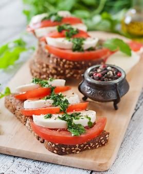 Bocadillos dietéticos útiles con mozzarella, tomate y pan de centeno.