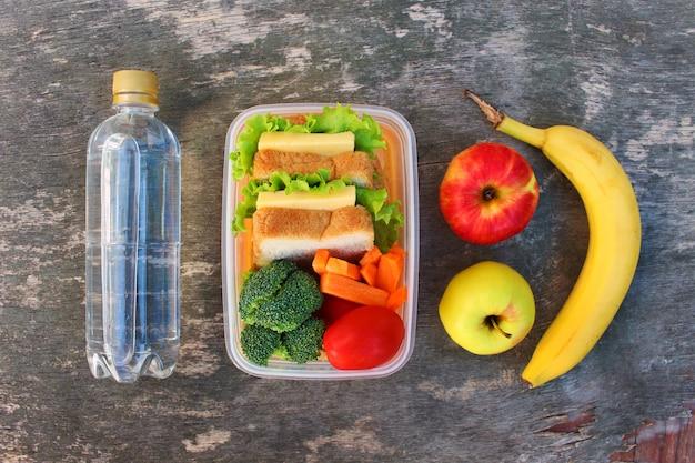 Bocadillos, frutas y verduras en caja de comida, agua.