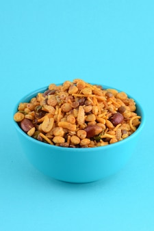 Bocadillos indios: mezcla (nueces tostadas con sal pimienta masala, legumbres, channa masala dal guisantes verdes) en un tazón azul en