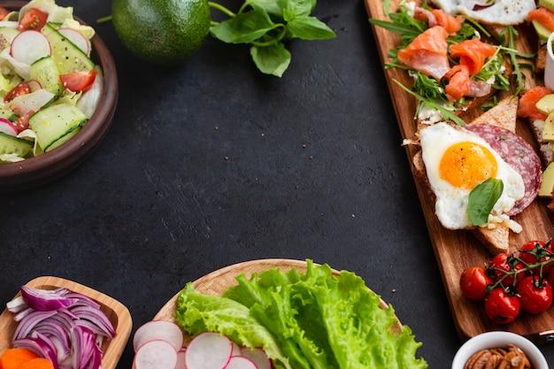 Bocadillos mediterráneos con brushettas, variedad de queso, salami, huevos y salmón sobre negro sobre tabla de madera, vista superior