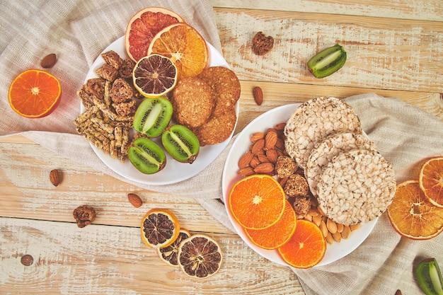 Bocadillos saludables: variedad de barra de granola de avena, arroz frito, almendra, kiwi, naranja seca