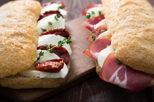 Bocadillos surtidos. sándwich caprese con mozzarella y tomates secos y ciabatta con jamón