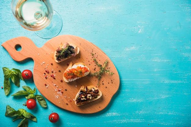 Bocadillos de tostadas con tomillo; albahaca y tomates y vino sobre fondo pintado.