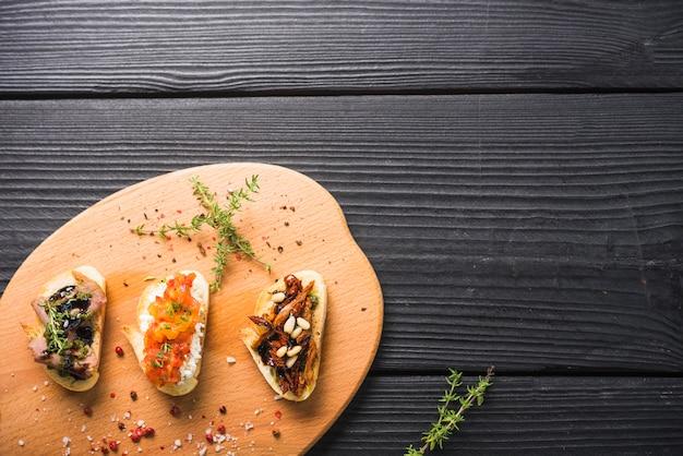 Bocadillos de tostadas con tomillo y semillas de granos de pimienta roja en una tabla de cortar