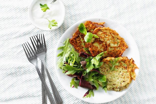 Bocadillos vegetarianos aperitivos calabacines buñuelos desayuno saludable vista superior blanca