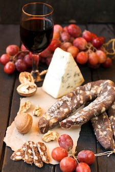Bocadillos para vino, queso con moho, uvas rosadas, nueces y chorizo seco