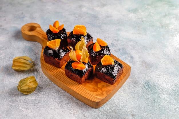 Bocaditos de pastel de chocolate con salsa de chocolate y con frutas, frutos del bosque.