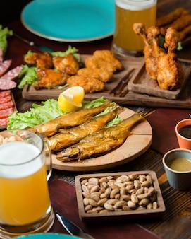 Bocaditos de pescado seco, nuggets de pollo y pistachos con un vaso de cerveza.