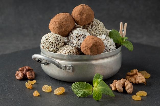 Bocados energéticos con cacao en polvo, semillas de sésamo y hojuelas de coco en una cacerola pequeña sobre una mesa gris