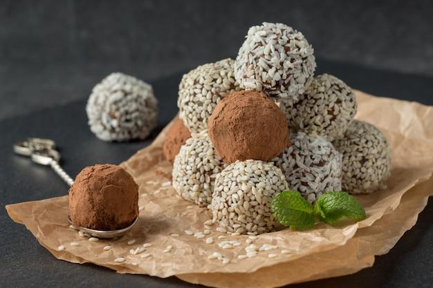 Bocados energéticos con cacao en polvo, semillas de sésamo y hojuelas de coco sobre pergamino