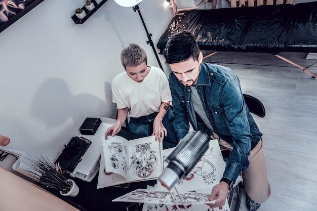 Bocetos y diseños. maestra de tatuajes inusual y su cliente masculino buscan diseños interesantes mientras están sentados en la esquina de su oficina