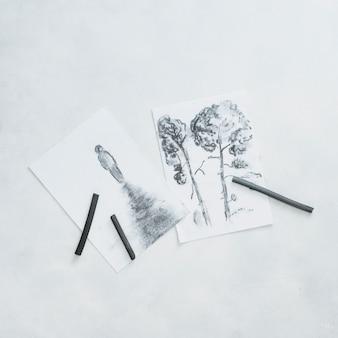 Bocetos hermosos y lápiz de carbón de leña aislados en el fondo blanco