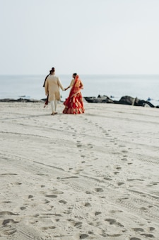 Boda hindú pareja camina a lo largo de la costa del océano