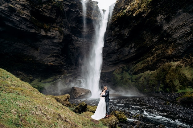 Boda en islandia de destino cerca de la cascada de kvernufoss, la pareja de novios está de pie cerca de la cascada