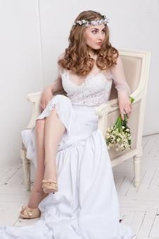 Boda. joven, gentil y tranquila novia en velo blanco clásico mirando hacia otro lado