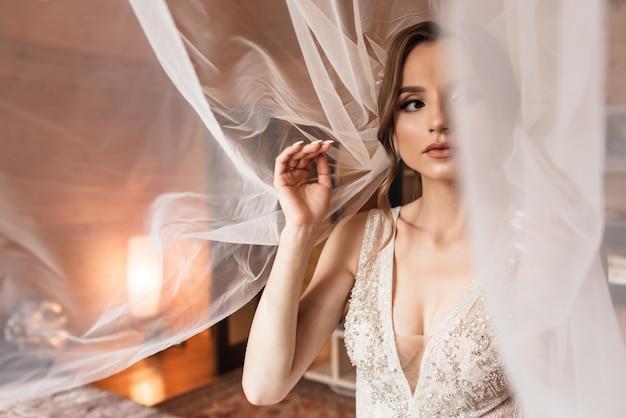 Boda. joven novia tranquila y apacible en velo blanco clásico mirando a otro lado