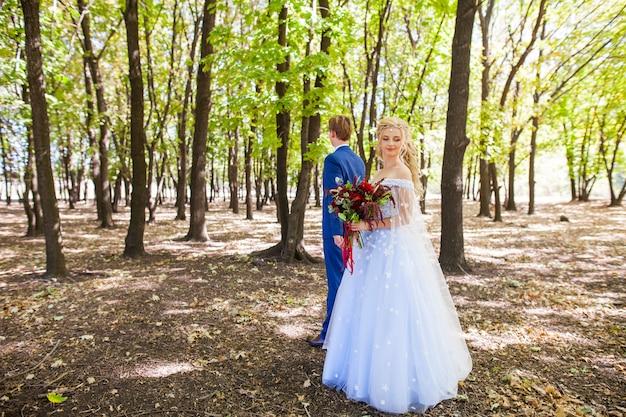 Boda de una joven pareja con un paseo por el parque verde.