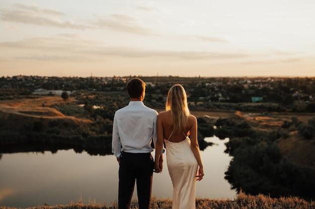 Boda en la montaña con río. el novio sostiene suavemente la mano de la novia.