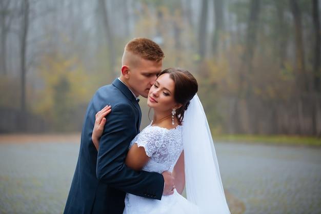 Boda novia y el novio besándose amorosa pareja con ramo de rosas flores en día de novia de invierno disfrute de un momento de felicidad y diversión. juguetona recién casada mujer mujer y hombre enamorado. hermosa novia