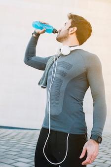 Bode hidratante del hombre deportivo después del entrenamiento