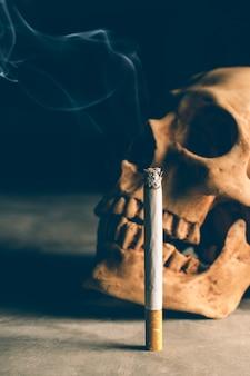 Bodegón abstracto cráneo de un esqueleto con cigarrillo encendido, dejar de fumar campaña con copyspace.