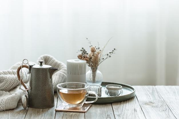 Bodegón acogedor con taza de té, velas y elemento tejido en el espacio de copia de fondo borroso.