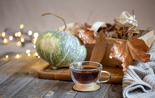 Bodegón acogedor con té y artículos decorativos, luces brillantes de fondo.