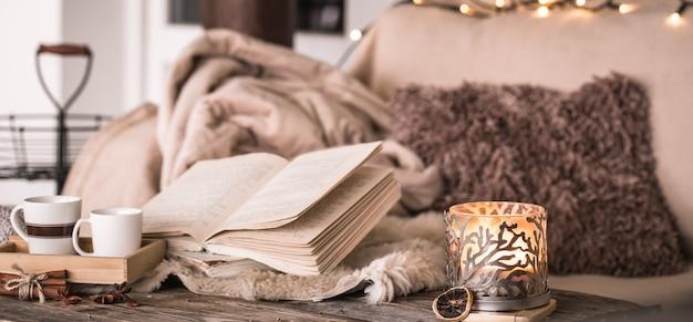 Bodegón ambiente hogareño en el interior con tazas, un libro y velas, en la pared de colchas acogedoras