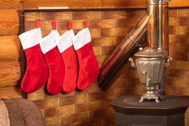Bodegón de año nuevo de cuatro calcetines rojos de año nuevo para regalos, una chimenea en el fondo de una pared de madera