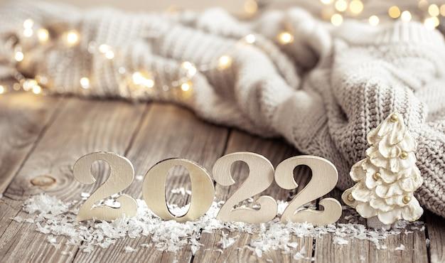 Bodegón de año nuevo con número decorativo del próximo año con detalles de decoración sobre fondo borroso.