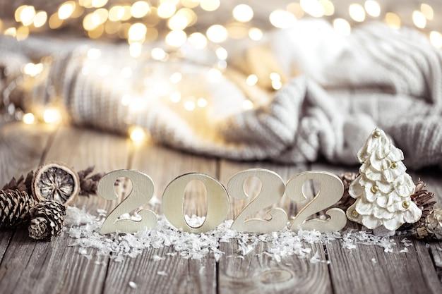 Bodegón de año nuevo con número decorativo del próximo año sobre una superficie de madera contra un fondo borroso.