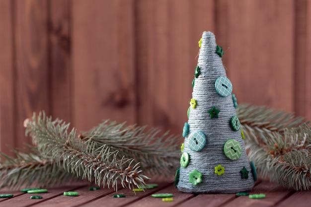 Bodegón de año nuevo con ramas de abeto y árbol de navidad hecho a mano de cuerda y botones.