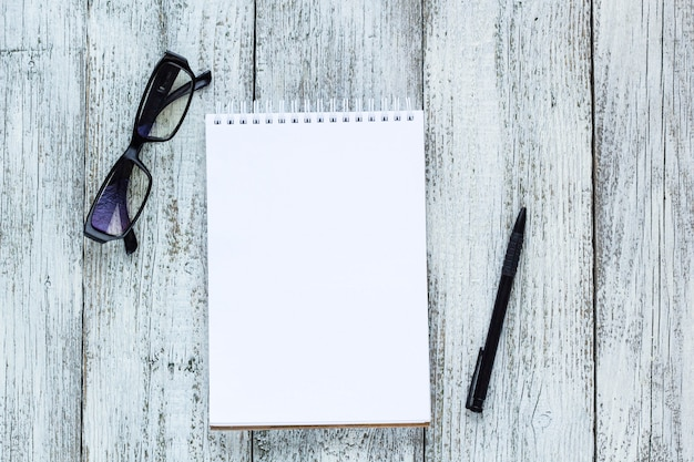 Bodegón en blanco y negro: bloc de notas en blanco abierto, cuadernos, bolígrafo, gafas.