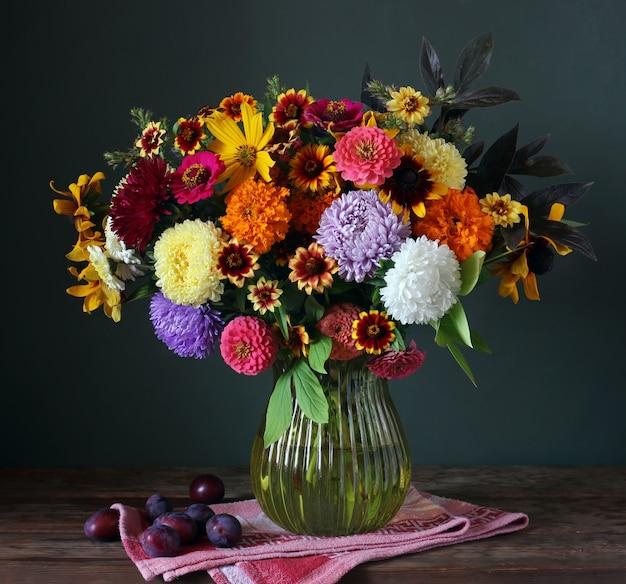 Bodegón con bouquet otoñal en jarrón y ciruelas en oscuridad.