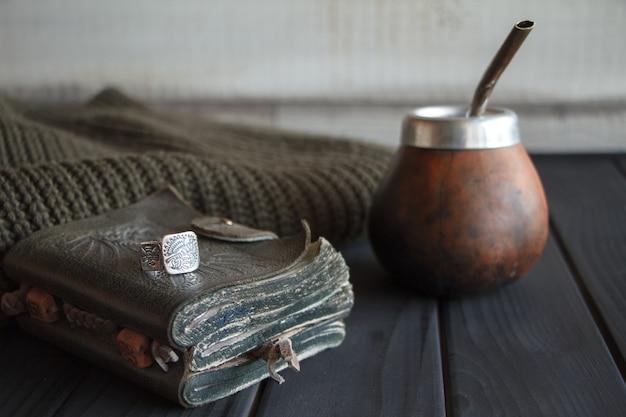 Bodegón de calabaza artesanal artesanal de calabaza de cuero con té de yerba mate con paja, cuaderno de cuero, suéter y anillo en una mesa pintada de negro,
