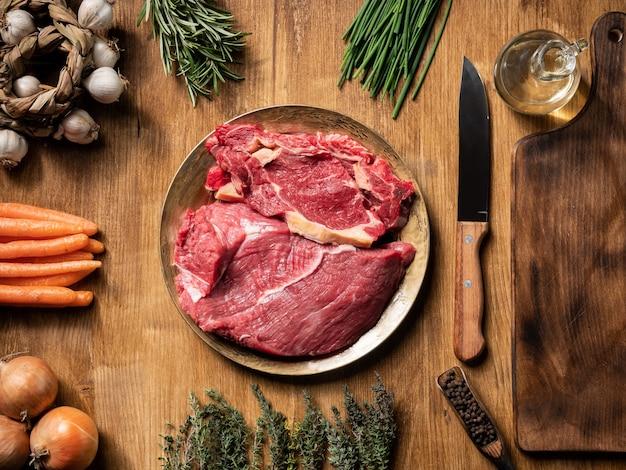 Bodegón de carne cruda con verduras en mesa de madera. vegetales verdes. frijoles de pimienta.