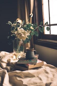 Bodegón composición de taza de té, libros y flores.
