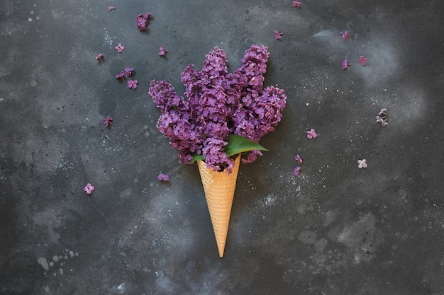 Bodegón creativo de lila rosada en cono de helado de gofres sobre una mesa negra vintage