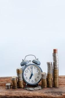 Bodegón, despertador y monedas con el tiempo es tiempo, vertical.