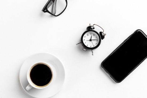 Bodegón, despertador vintage y taza de café en mesa blanca