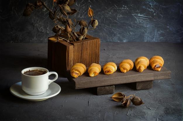 Bodegón de estilo antiguo con cruasanes y una taza de café.