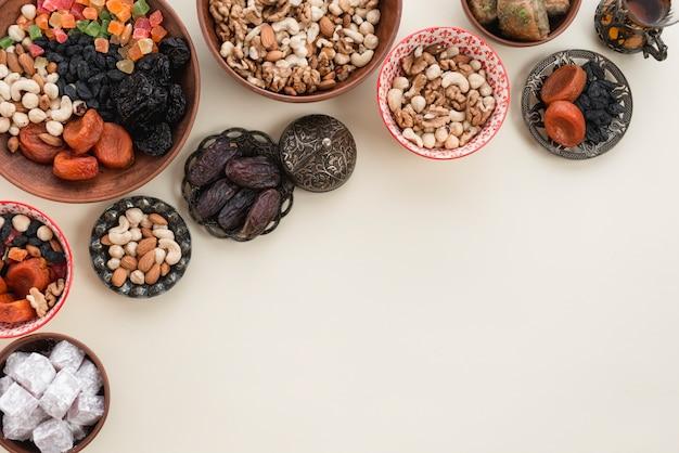 Bodegón festivo con ramadan oriental de frutos secos; nueces; fechas y lukum sobre fondo blanco