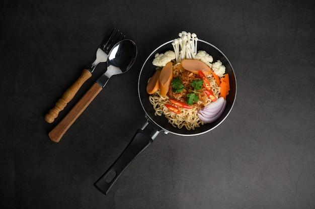 Bodegón con los fideos en una sartén, tenedor y cuchara en el piso de cemento negro.