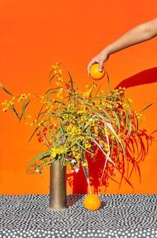 Bodegón de flores de primavera con sombra dura y una mano con una naranja.