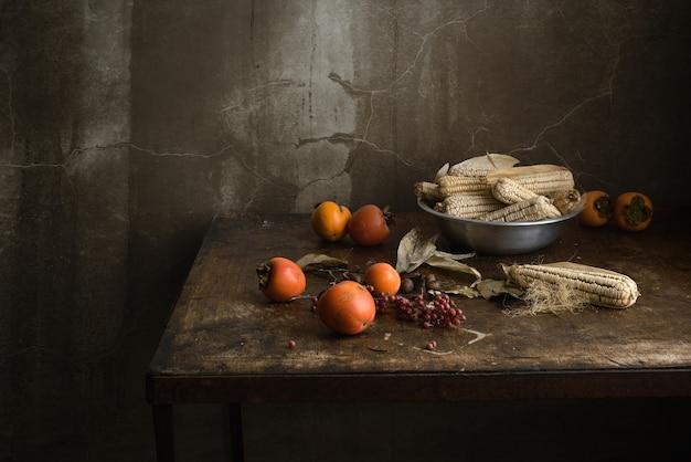 Bodegón con frutas y maíz en un recipiente de aluminio sobre una mesa antigua de madera