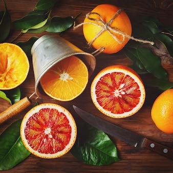 Bodegón con frutas naranjas y hojas verdes