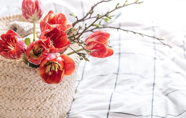 Bodegón con hermosos tulipanes rojos en la canasta.