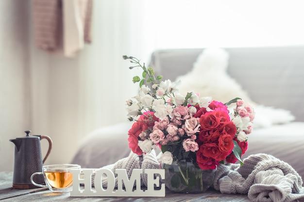 Bodegón con una inscripción en casa y un jarrón de flores.