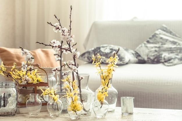 Bodegón con jarrones con flores de primavera en el salón.