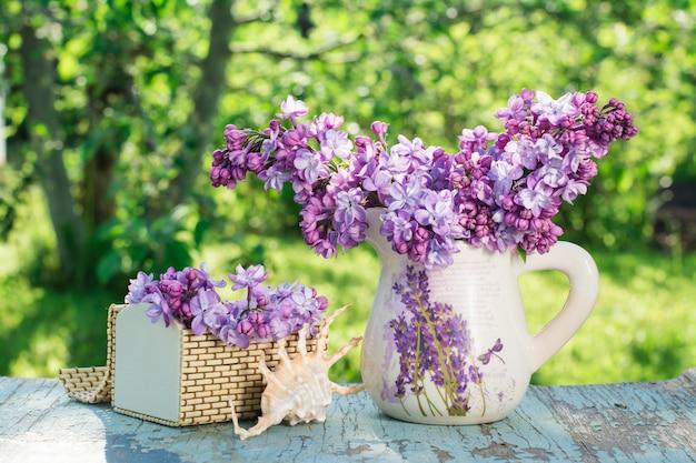 Bodegón con lila en una jarra, un ataúd, un caparazón sobre una mesa de madera con el telón de fondo de vegetación